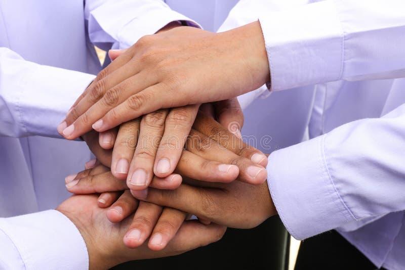 Grupo diverso de trabajadores con sus manos junto fotografía de archivo
