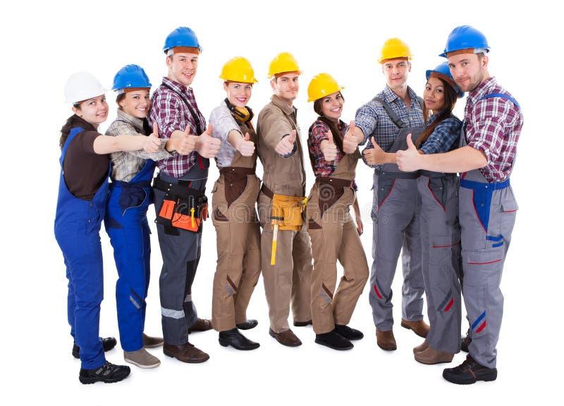 Grupo diverso de trabajadores dando los pulgares para arriba fotografía de archivo