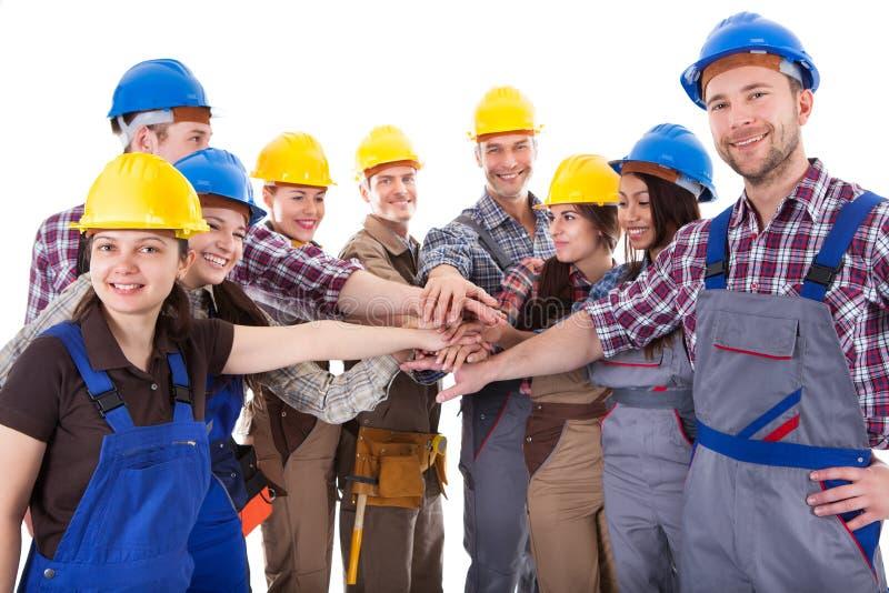 Grupo diverso de trabalhadores da construção que empilham as mãos foto de stock