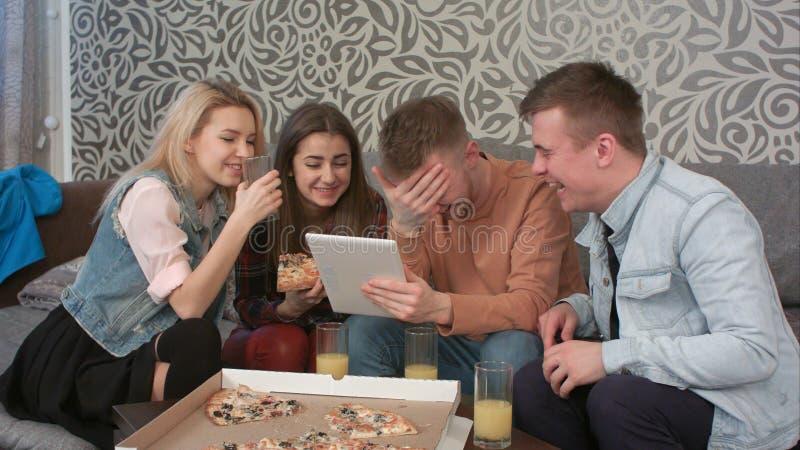 Grupo diverso feliz de amigos que riem do que vê na tela de uma tabuleta do computador imagem de stock
