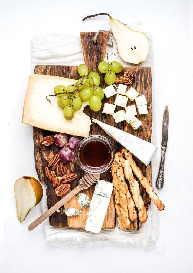 Grupo do aperitivo do queijo Vários tipos de queijo, de mel, de uvas, de pera, de porcas e de varas do grissini do pão em de made foto de stock