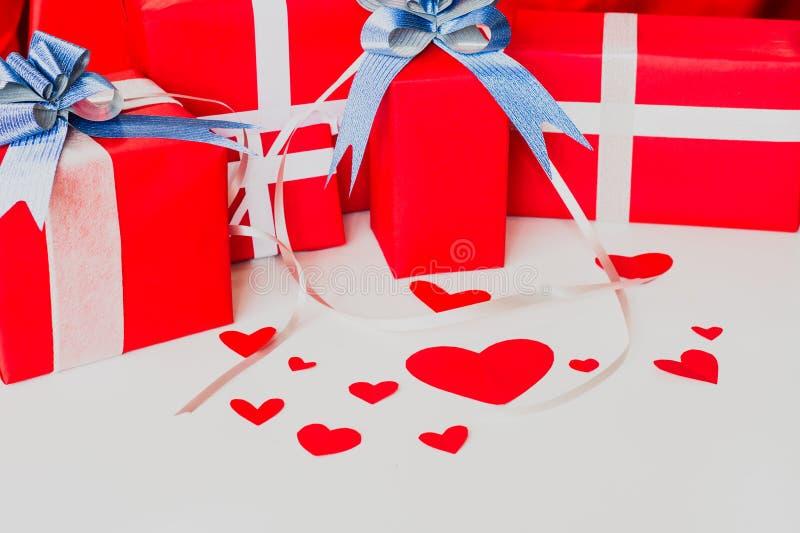 Grupo do dia de são valentim de caixas vermelhas do presente, com curva e a fita azuis, com forma de papel do coração, no fundo b imagens de stock royalty free