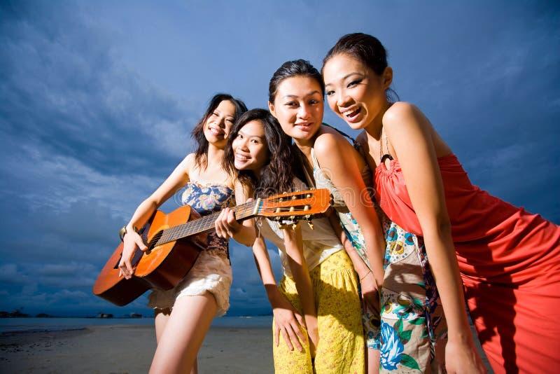 Grupo do divertimento de meninas que jogam a guitarra na praia foto de stock royalty free