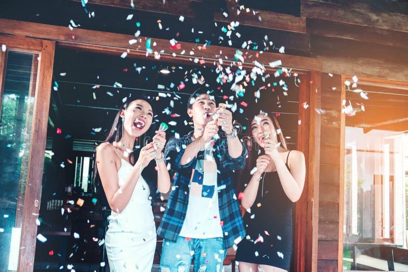 Grupo do partido da celebração de jovens asiáticos que guardam os confetes h fotografia de stock
