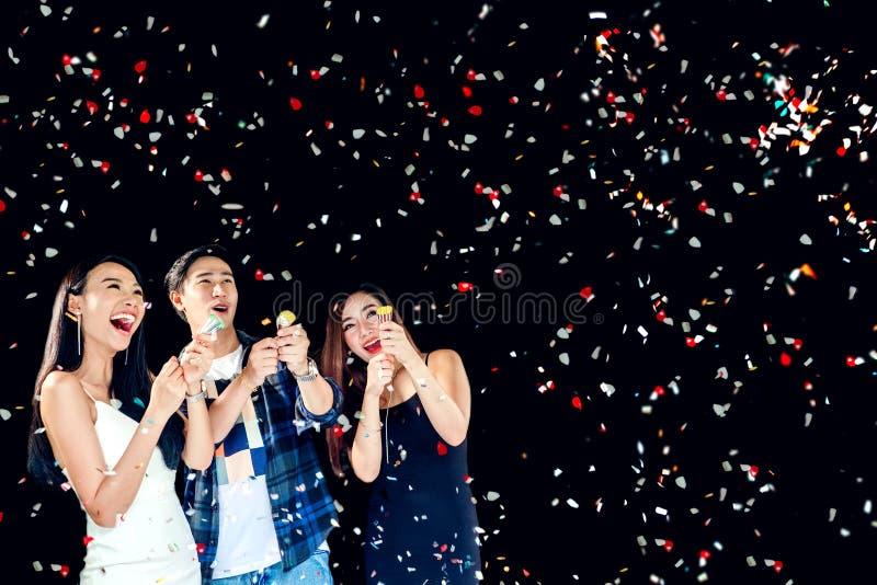 Grupo do partido da celebração de jovens asiáticos que guardam os confetes h foto de stock