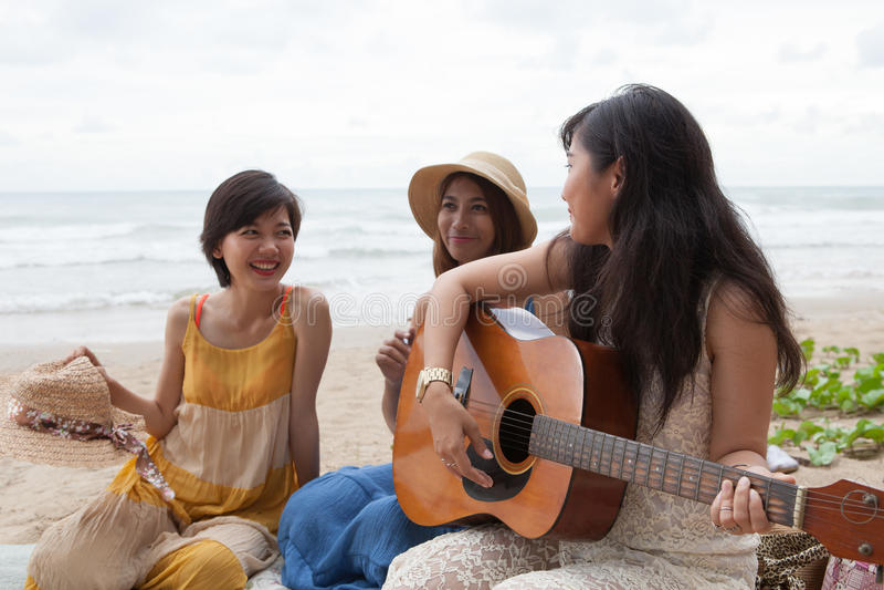 Grupo do retrato de mulher asiática nova que joga a guitarra na praia do mar imagem de stock