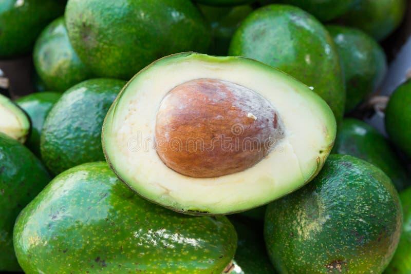 Grupo dos abacates orgânicos maduros crus inteiros e partidos ao meio no mercado dos fazendeiros Textura de seda da carne do poço fotografia de stock royalty free