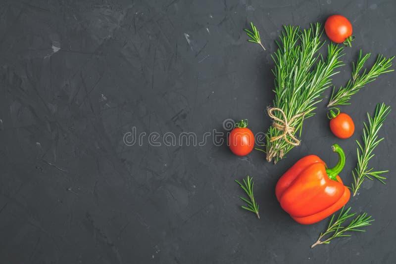 Grupo dos alecrins dos ramalhetes, da pimenta crua e dos tomates na superfície textured concreta da pedra preta foto de stock