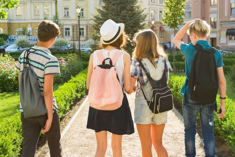 Grupo dos amigos felizes 13 dos adolescentes, 14 anos andando ao longo da rua da cidade Vista da parte traseira imagem de stock