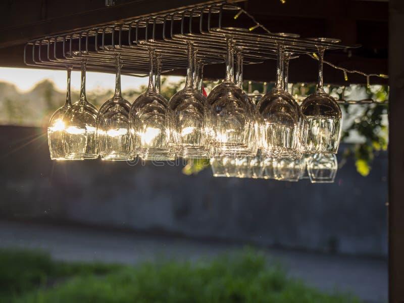Grupo dos cristais para o vinho ou o champanhe Reflexões de raios do sol no vidro no por do sol foto de stock royalty free