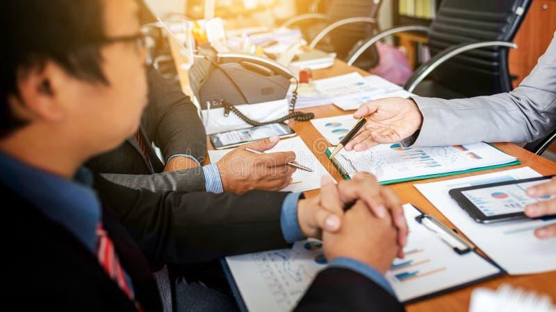 Grupo dos empresários masculinos que discutem o projeto da gestão durante o trabalho junto e a análise do comércio e da experiênc foto de stock