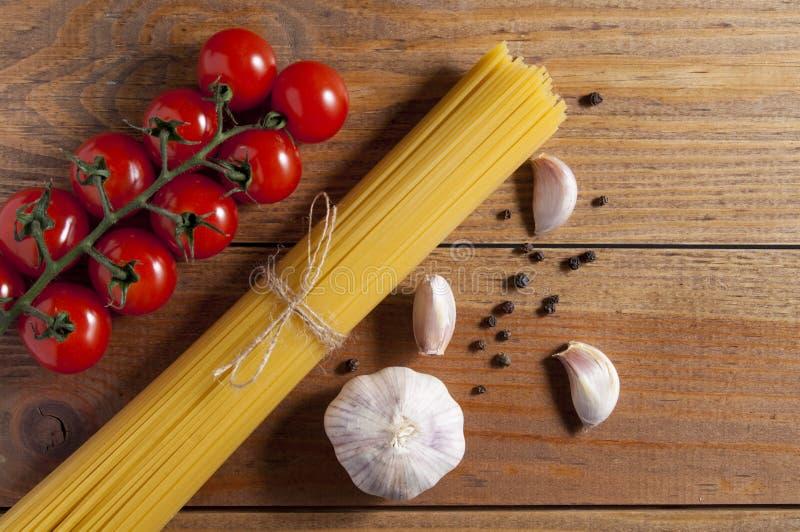 Grupo dos espaguetes crus amarrados com corda, cereja dos tomates, bulbo e fatias de alho e de pimenta no fundo de madeira marrom fotografia de stock royalty free