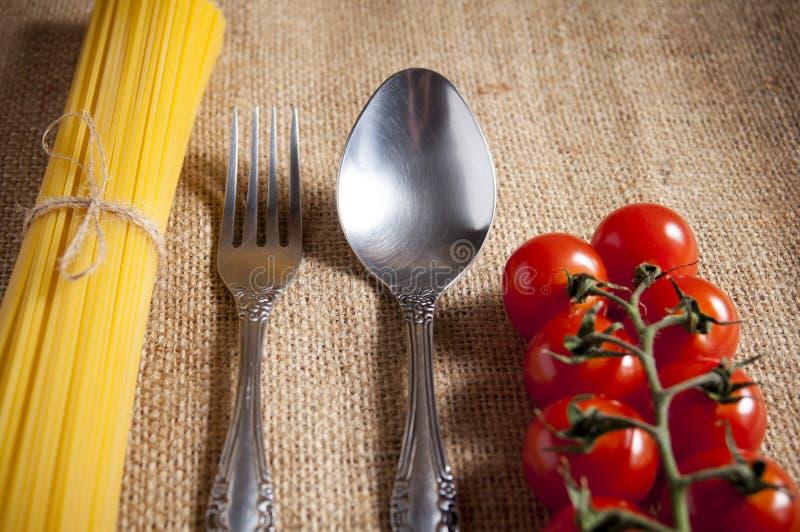 Grupo dos espaguetes crus amarrados com corda, tomates cereja, colher e forquilha na serapilheira fotos de stock