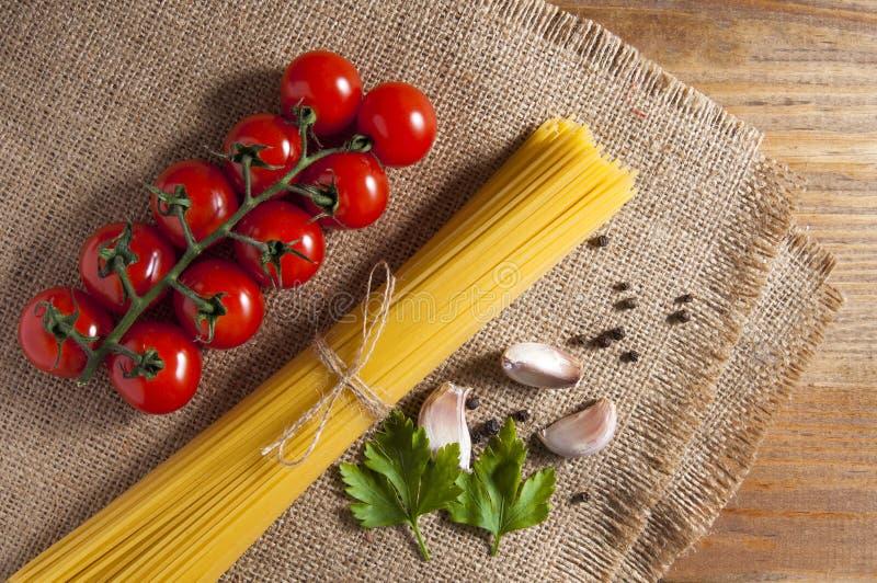Grupo dos espaguetes crus amarrados com corda, tomates cereja, fatias de alho, folhas da salsa e pimenta na serapilheira, tudo em foto de stock