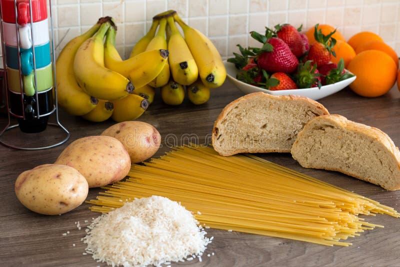 Grupo dos hidratos de carbono para a dieta - pão, arroz, batatas e massa em uma tabela de madeira imagem de stock