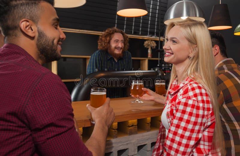 Grupo dos jovens na barra, par que senta-se no bar contrário de madeira, cerveja da bebida fotos de stock royalty free