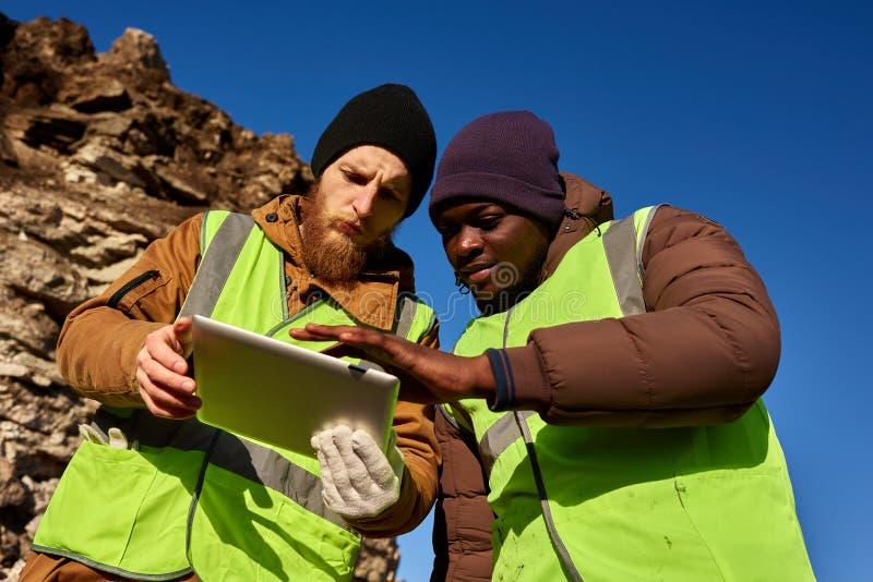 Grupo dos mineiros que inspeciona a terra fotografia de stock
