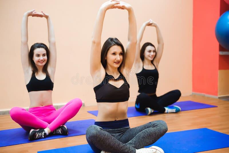 Grupo dos povos desportivos em um gym - amigos desportivos felizes em uma sala de peso ao treinar - conceitos sobre o estilo de v imagem de stock royalty free