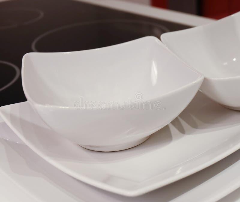 Grupo dos pratos, das bacias e das placas brancos de porcelana foto de stock