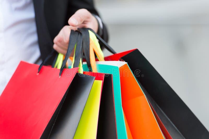 Grupo dos sacos de compras nas mãos masculinas exteriores, ascendente próximo Planeie suas compras adiantado Pontas de compra suc fotos de stock