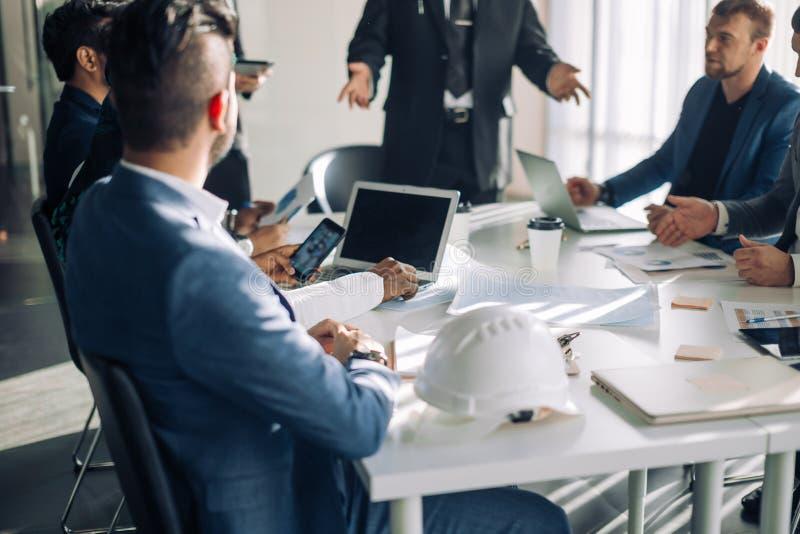 Grupo dos trabalhadores de escritório masculinos em uma apresentação da sala de reuniões, fim acima imagem de stock
