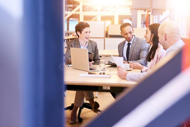 Grupo eclético de quatro profissionais do negócio que conduzem uma reunião fotografia de stock royalty free