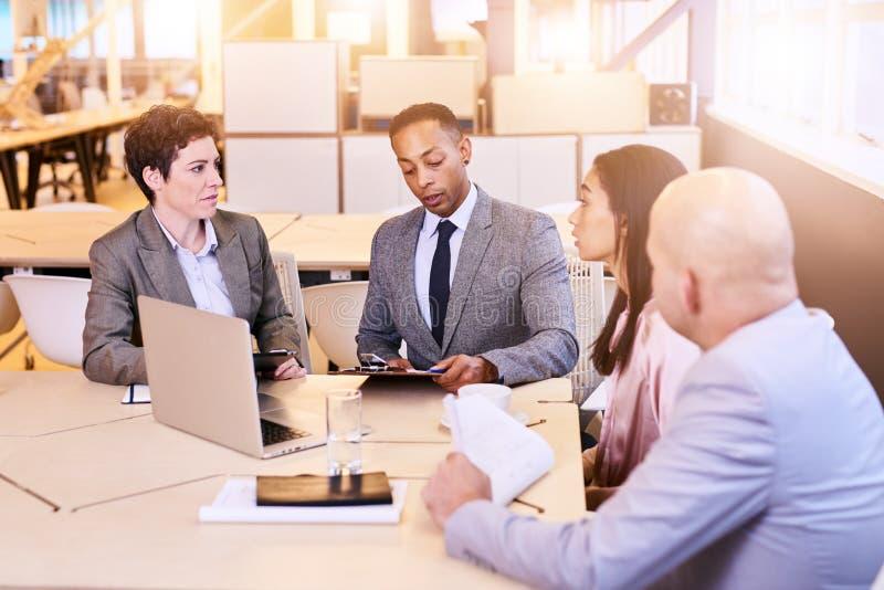 Grupo eclético de quatro profissionais do negócio que conduzem uma reunião imagens de stock