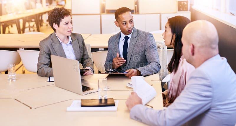 Grupo eclético de quatro profissionais do negócio que conduzem uma reunião imagens de stock royalty free