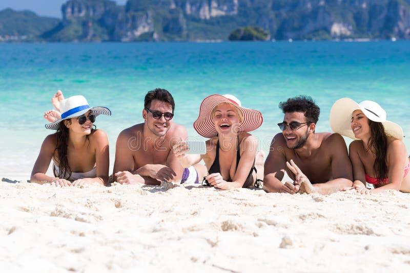 Grupo el vacaciones de verano de la playa, playa de mentira sonriente feliz de la gente joven de la arena de los amigos fotografía de archivo