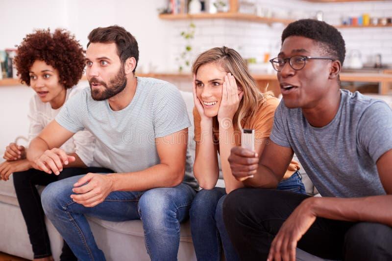 Grupo emocionado de amigos que se sientan en Sofa And Watching Sports On TV fotografía de archivo