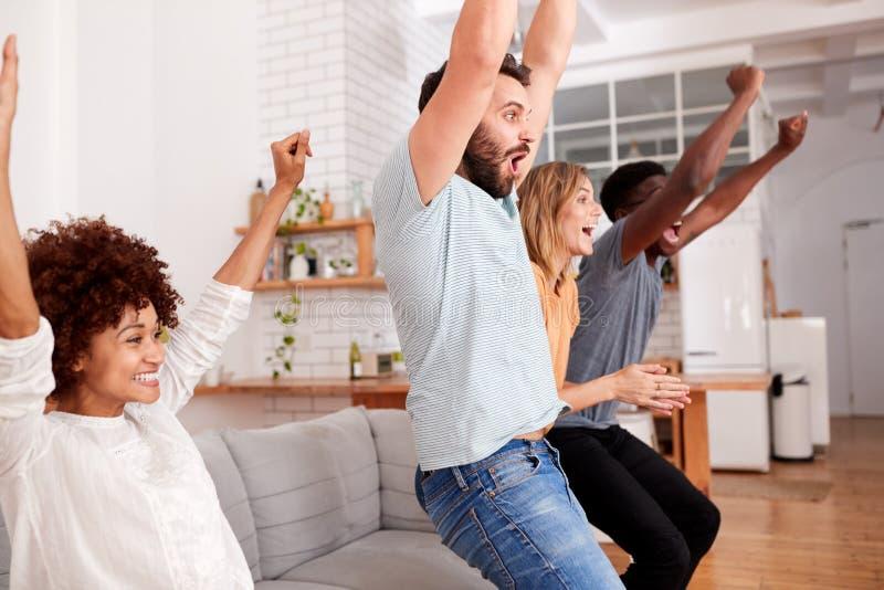 Grupo emocionado de amigos que se sientan en Sofa Watching Sports On TV y que celebran imagen de archivo