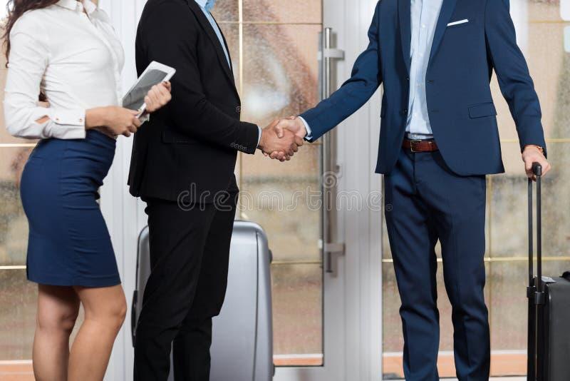Grupo en pasillo, dos hombre de negocios Meeting Handshake de Meeting Business People del recepcionista del hotel imagen de archivo libre de regalías