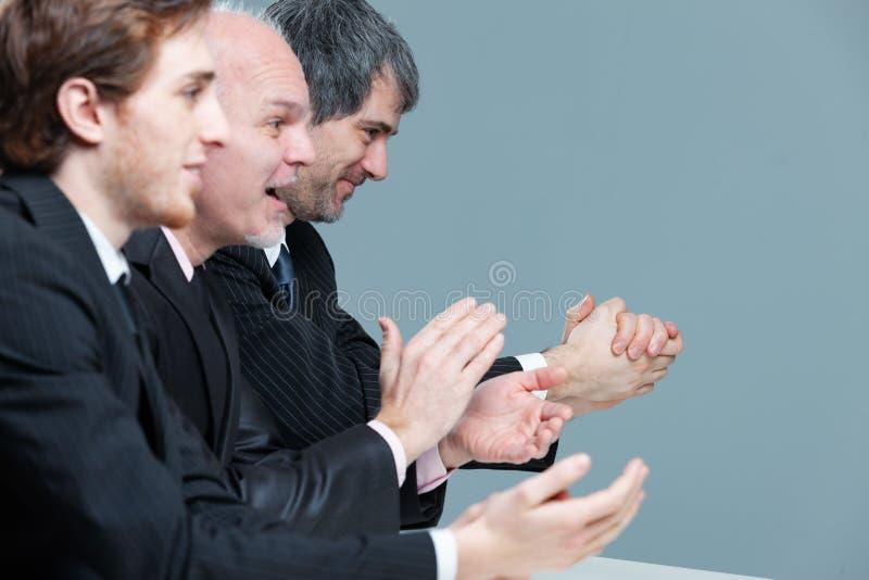 Grupo entusiástico de aplauso do homem de negócios fotografia de stock royalty free