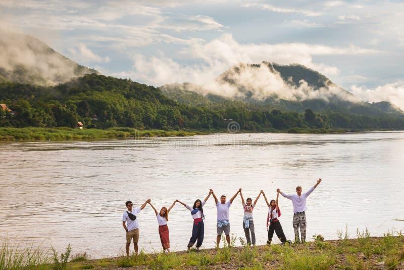 Grupo feliz de amigo con los brazos foto de archivo