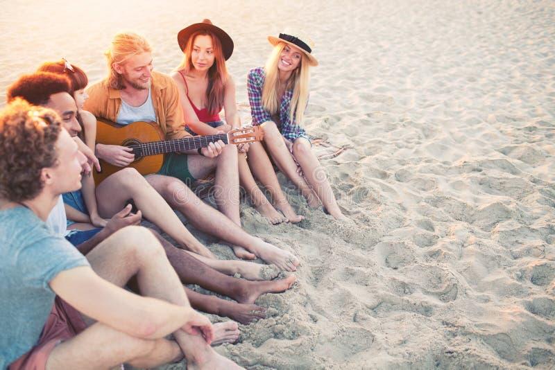 Grupo feliz de amigo que tem o partido na praia imagem de stock