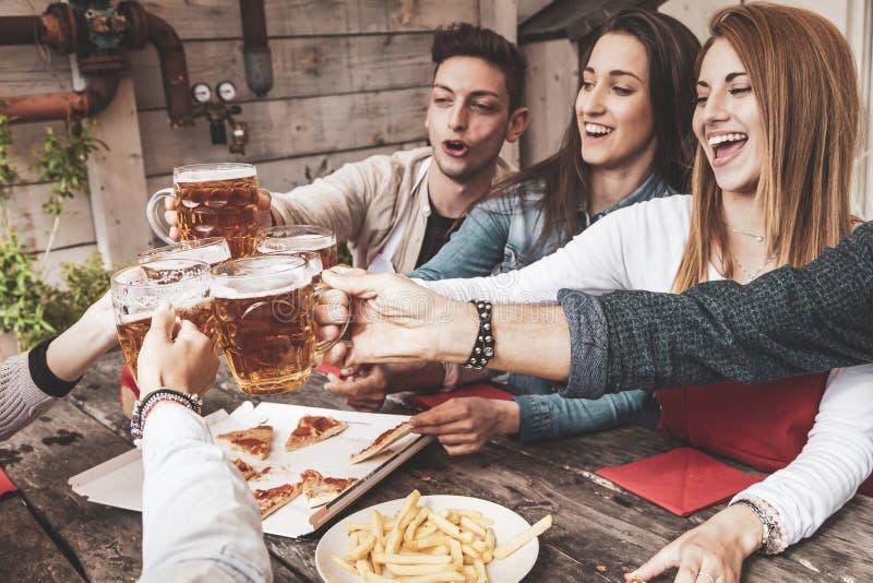 Grupo feliz de amigos que bebem a cerveja e que comem a pizza fotografia de stock royalty free
