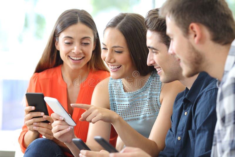 Grupo feliz de amigos que comprueban los teléfonos elegantes en casa imágenes de archivo libres de regalías