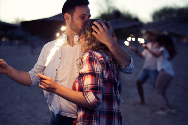 Grupo feliz de amigos que iluminam chuveirinhos e que apreciam a liberdade foto de stock royalty free