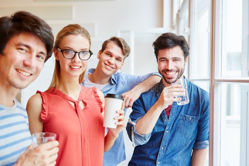 Grupo feliz de amigos que tomam uma ruptura do coffe fotografia de stock