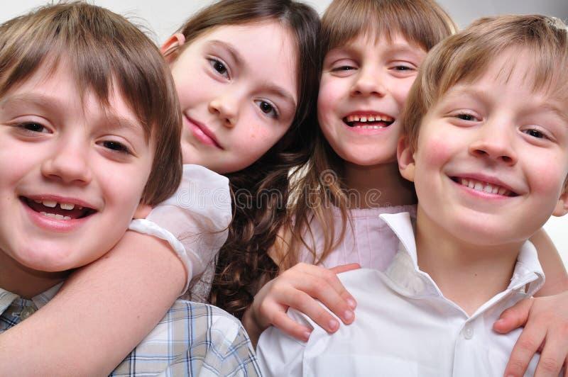Grupo feliz de crianças que abraçam junto fotografia de stock