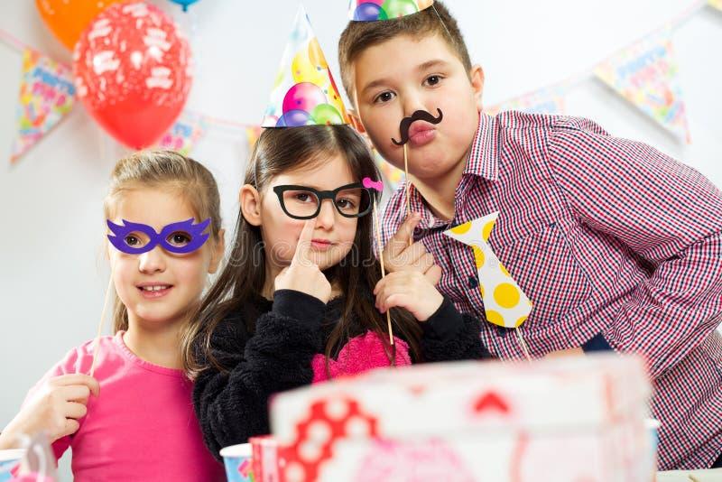 Grupo feliz de crianças que têm o divertimento na festa de anos foto de stock royalty free