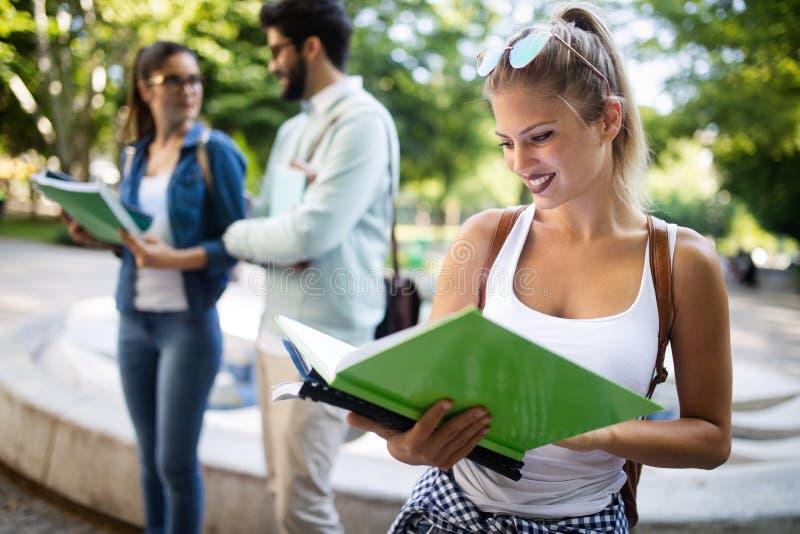 Grupo feliz de estudantes que estudam e que aprendem junto na faculdade imagem de stock
