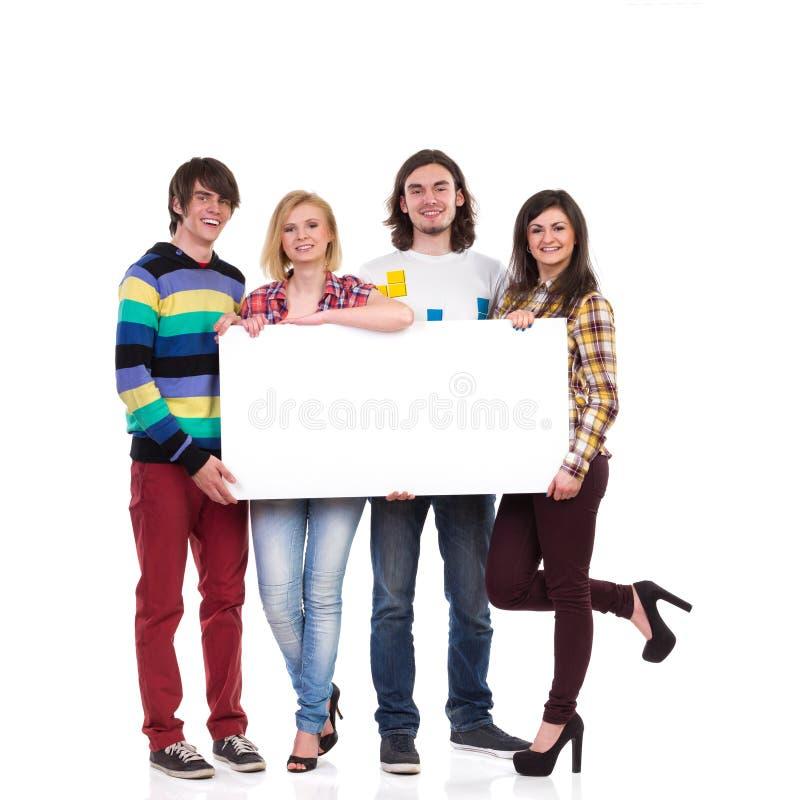Grupo feliz de estudantes que guardam a bandeira vazia fotografia de stock