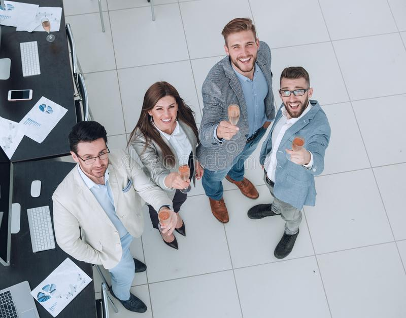 Grupo feliz de executivos novos que aumentam vidros do champanhe imagem de stock