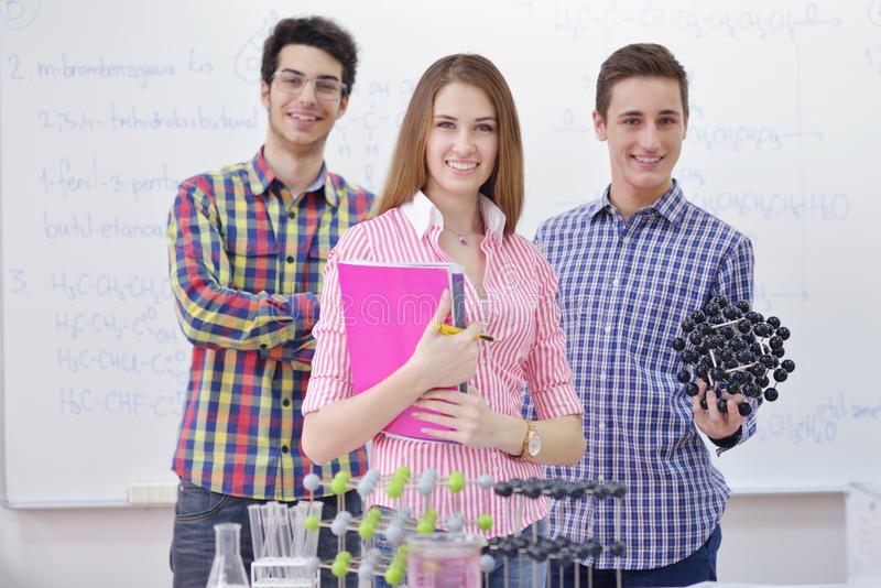 Grupo feliz de las adolescencias en escuela imagenes de archivo