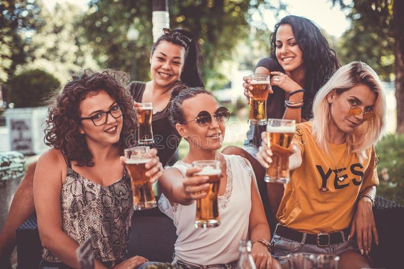 Grupo feliz de los mejores amigos femeninos que beben la cerveza - concepto de la amistad con los amigos femeninos jovenes que di foto de archivo