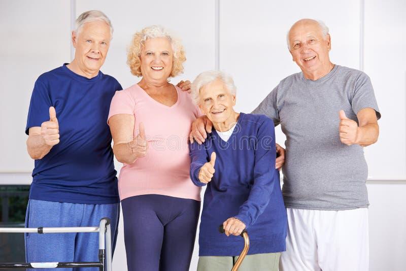 Grupo feliz de mayores que detienen los pulgares imagenes de archivo