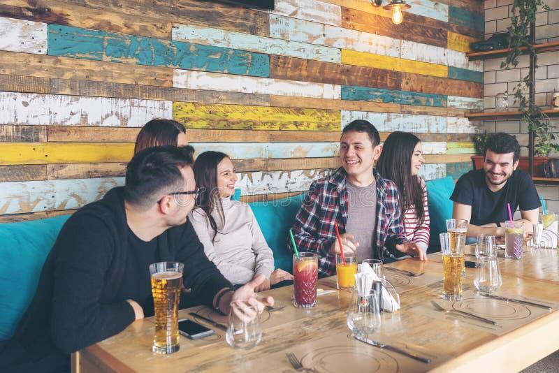 Grupo feliz de melhores amigos que comem a cerveja bebendo do divertimento ao esperar a ordem do alimento no restaurante imagem de stock