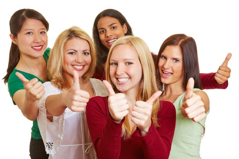 Grupo feliz de mulheres que mantêm os polegares fotografia de stock royalty free