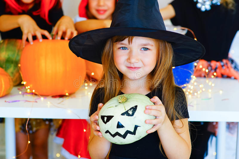 Grupo feliz de niños en trajes durante el partido de Halloween imagenes de archivo